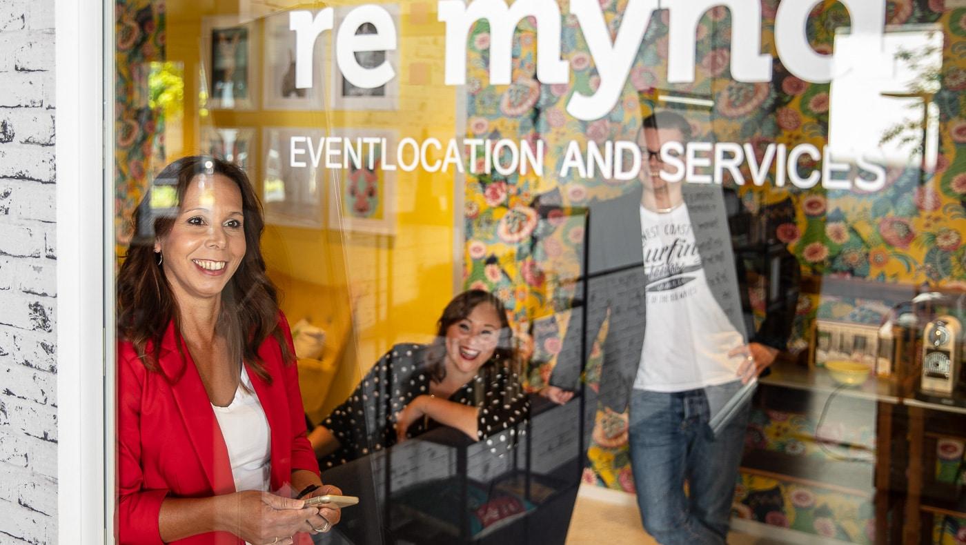 Corporate Fotografie Remynd Team hinter Glas lächelnd