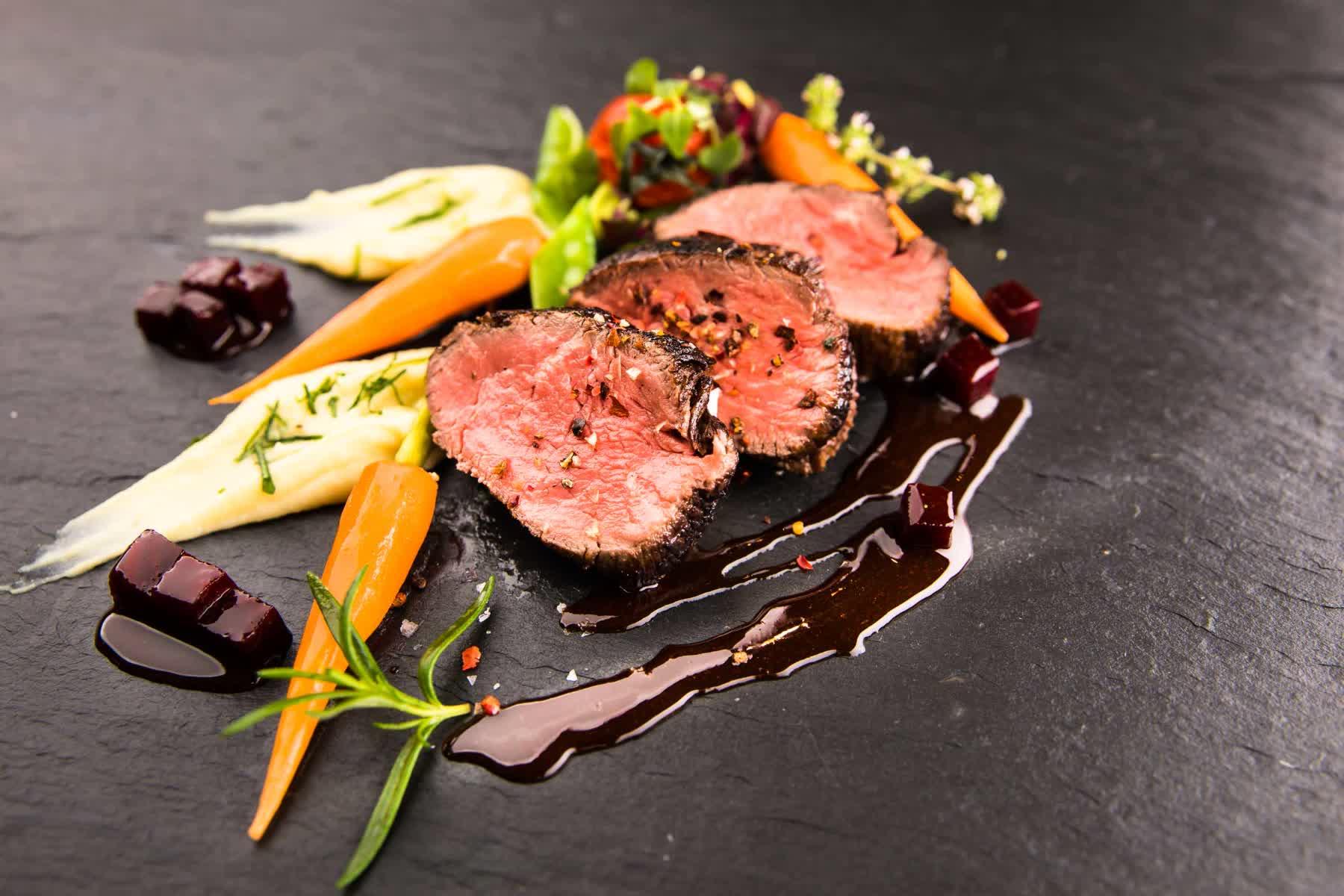 Fleisch mariniert auf Schieferplatte mit Gemüse
