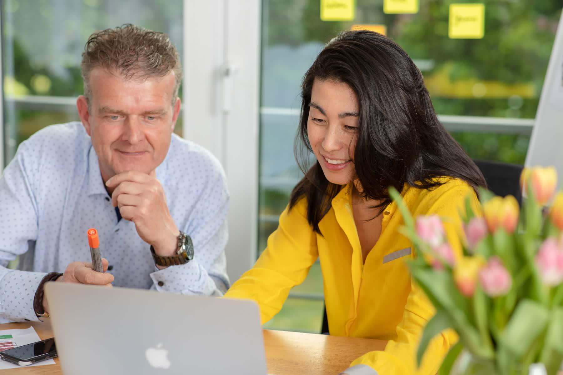 Corporate Fotografie Asiatische Frau im Gespräch mit einem Kollegen am Laptop