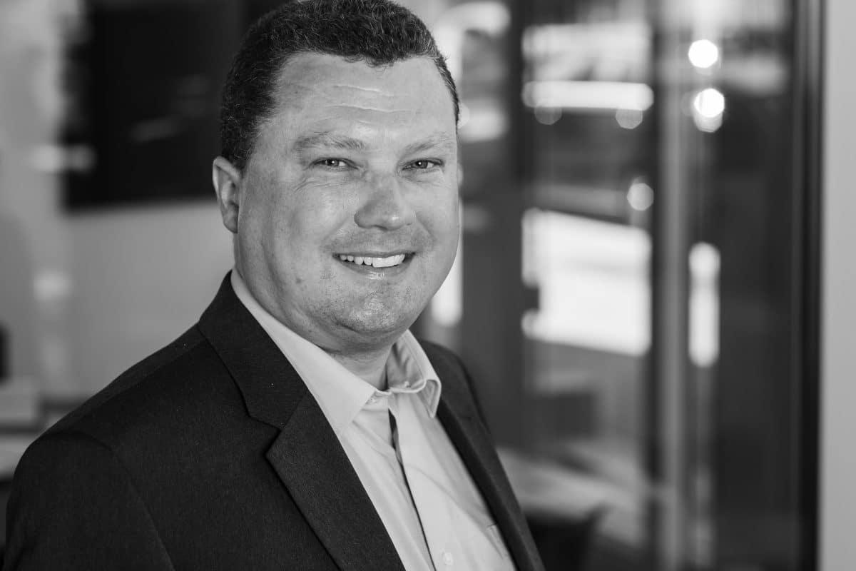 Businessportrait Schwarz Weiss lächelnder Mann