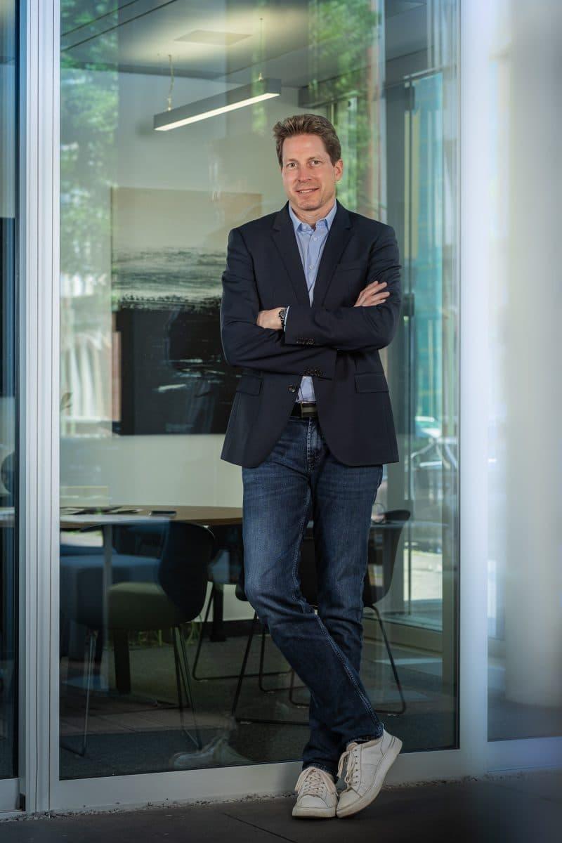 Businessportrait stehender Mann in dunklem Jacket an einer Wand