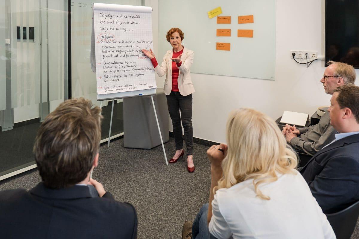 Frau am Flipchart in Aktion mit Teilnehmern in einem Meeting Raum