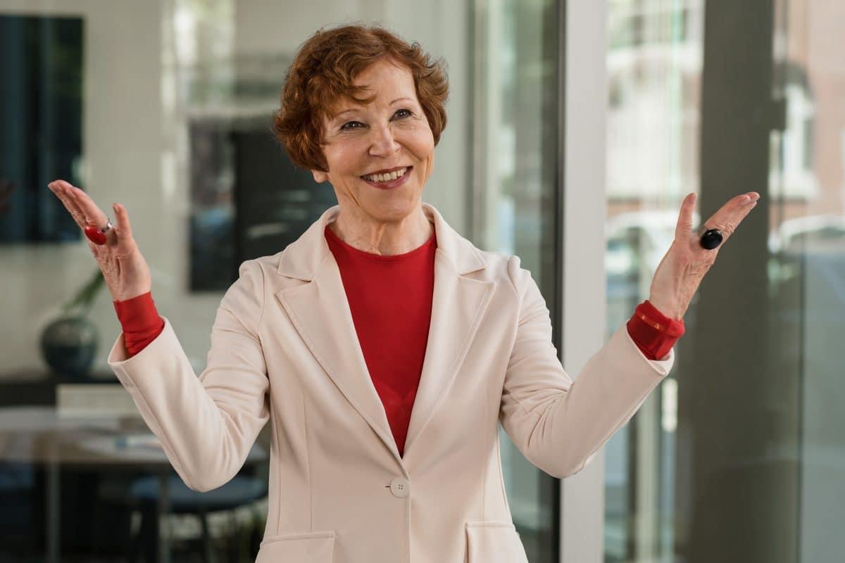 Businessportrait lächelnder Frau mit geöffneten Händen
